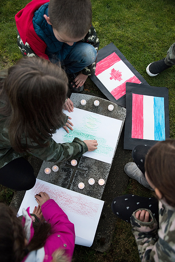 Students imprinting the name of a Canadian soldier by rubbing crayons over a pice of parchment. Ashley Martens photo.
