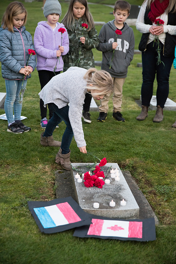A student laying a tulip at the grave on one Abbotsford soldier killed in the Second World War. Ashley Martens photo.